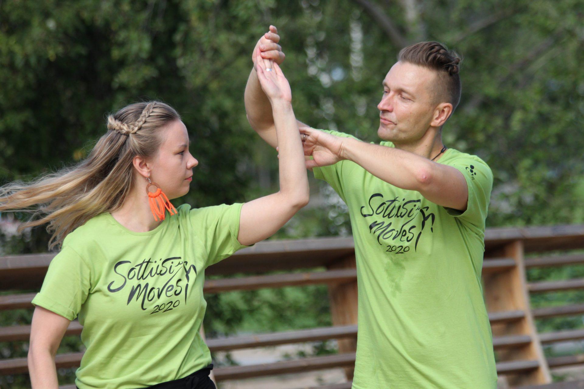 Pari tanssii ulkona SottiisiMovesin vihreissä t-paidoissa. Taustalla näkyy vehreitä puita.