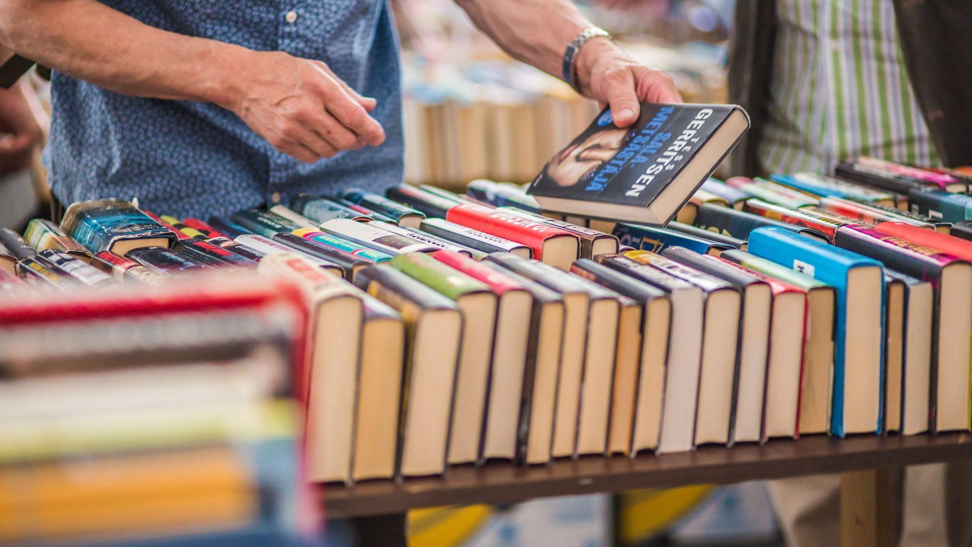 Kuvassa käsipari ja kirjoja rivissä.