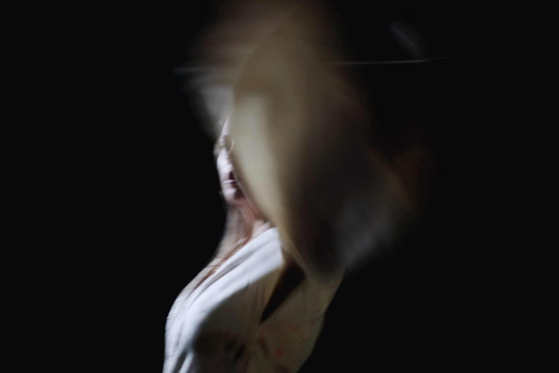 Selma Juudit Alessandran epätarkka kuva, jossa naishahmo on vaaleassa vaatteessa mustalla taustalla ja heilauttaa kättään.