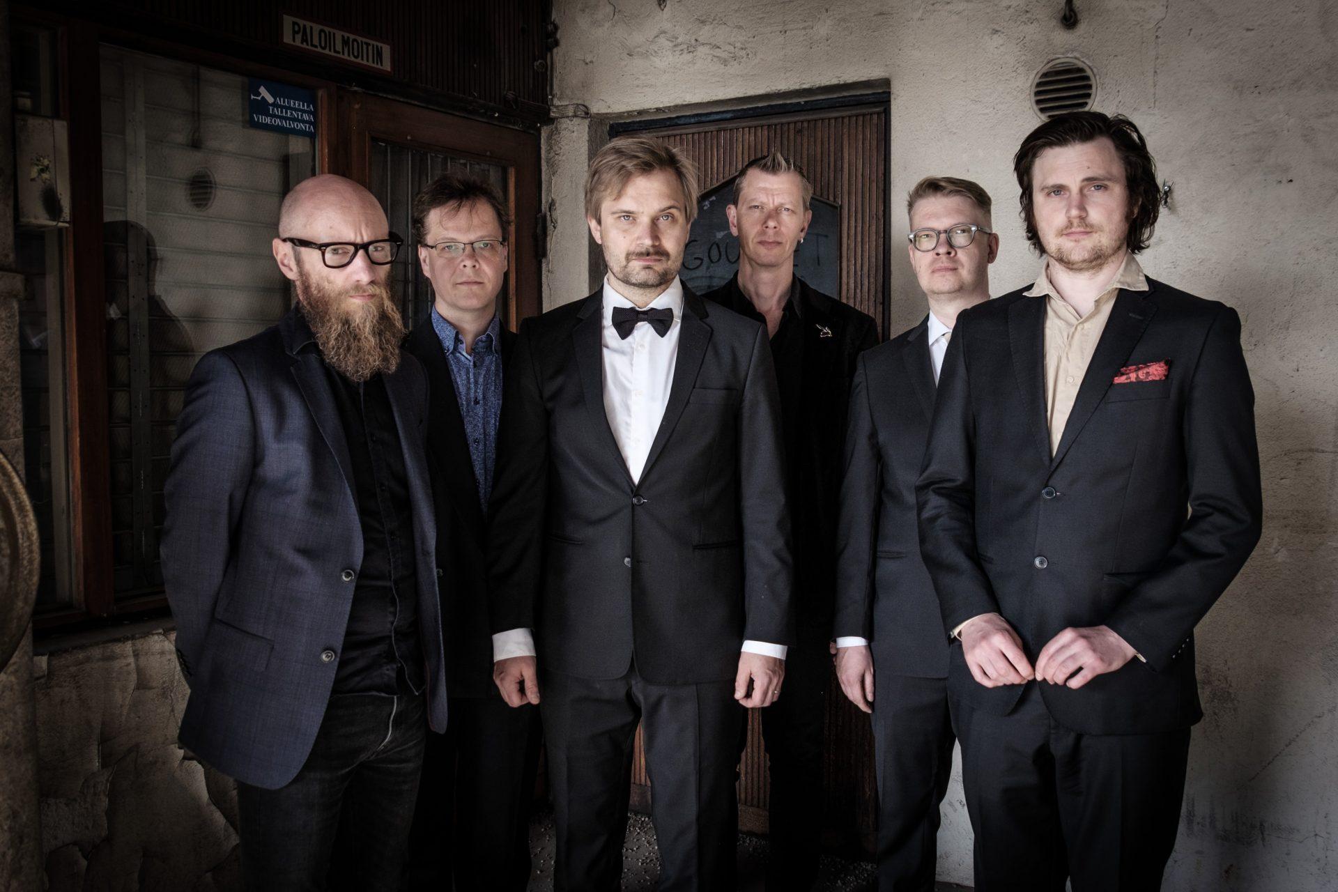 Gourmet-yhtyeen kuusi soittajaa seisoo vieretysten tummissa puvuissa ja katsoo kameraan.