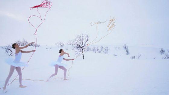 Kaksi tanssijaa heittää lassonaruja ilmaan. Toinen lasso on keltainen ja toinen punainen. Tanssijoilla on valkoiset balettipuvut ja ympäristö on luminen Lapin erämaa.