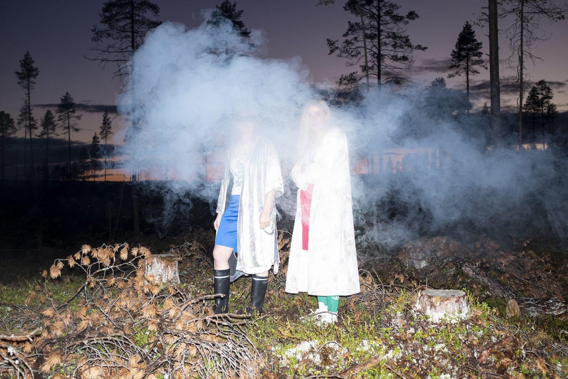 Maustetytöt-yhtyeen kaksi jäsentä seisoo savupilven keskellä hämärässä metsässä, kumisaappaissa ja pitkissä valkoisissa takeissa.