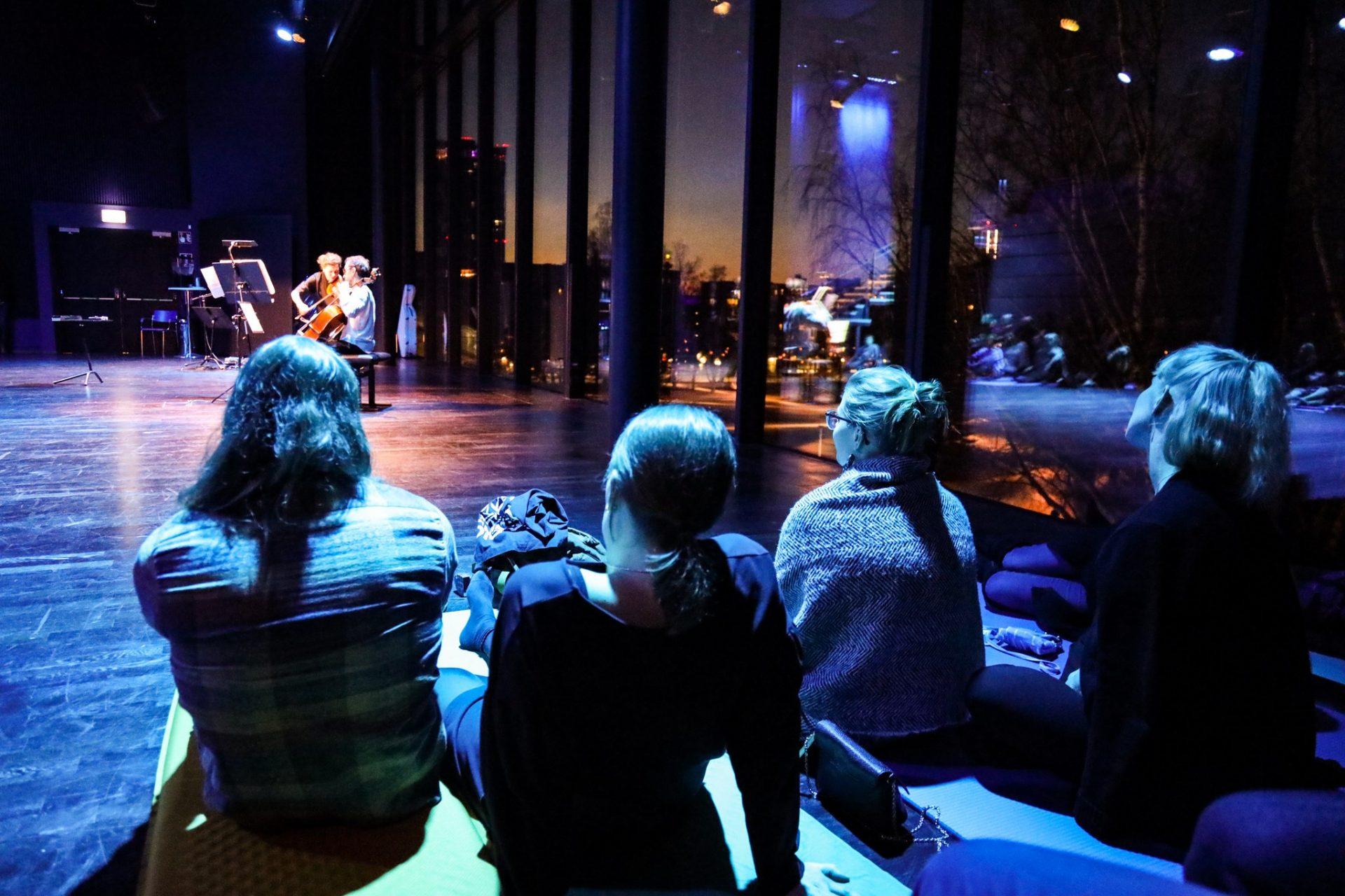 Yleisö istuu hämärän salin lattialla kuuntelemassa konserttia. Salissa on lasiset seinät, joista näkyy ulos talviseen Sorsapuistoon.