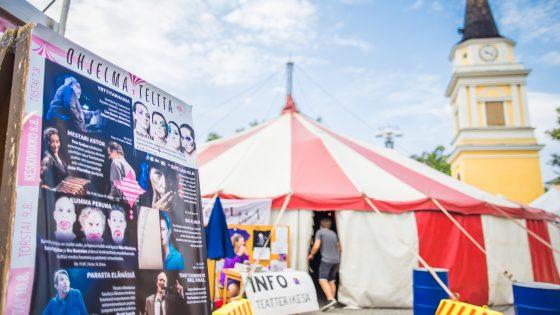 Julistetaulu. Taustalla puna-valkoinen teltta.