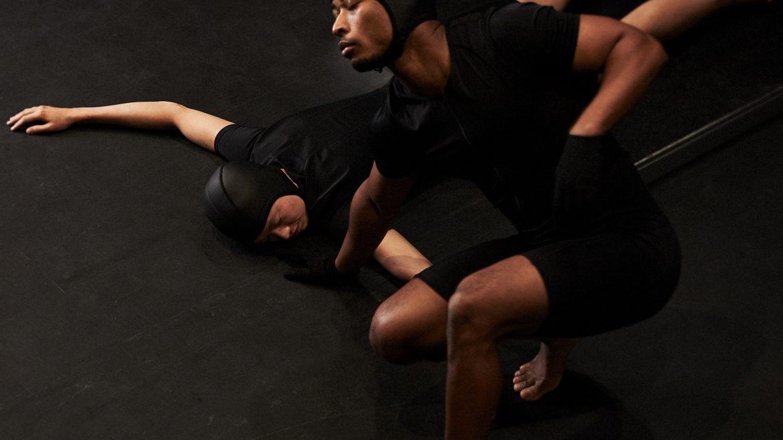Kaksi miestä esittää teosta Hetken keltainen. Toinen miehistä makaa lattialla