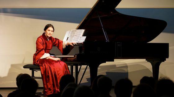Viktoria Papayana istumassa flyygelinsä äärellä.