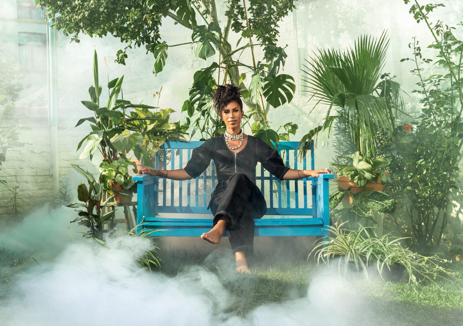 Nainen istuu sinisellä penkillä kasvien ympäröimänä